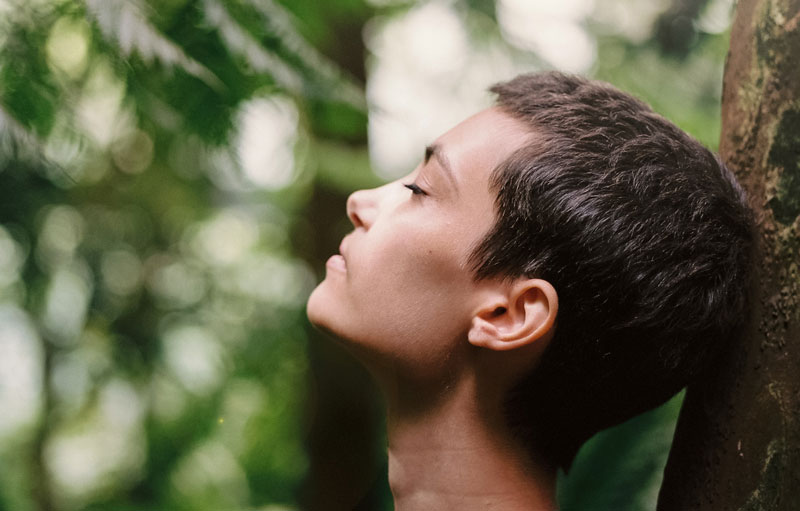 woman breathing deeply in a forest